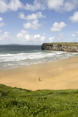 view of lone man at beach and cliffs in Ballybunion