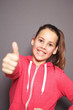 Cheerful young girl giving a thumbs up