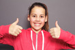 Enthusiastic young girl giving thumbs up