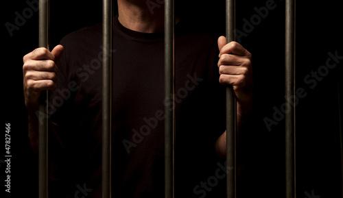 Leinwanddruck Bild prisoner behind bars