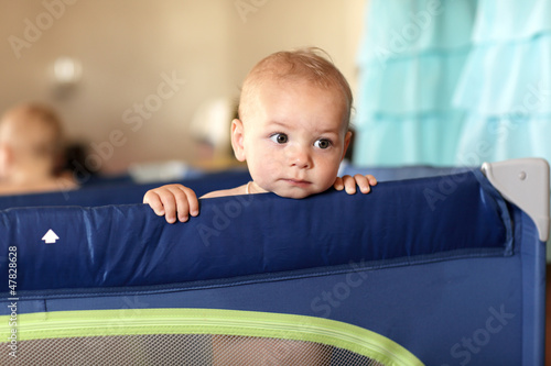 Pensive baby at playpen