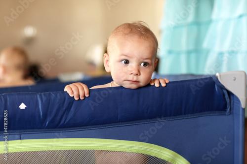 Pensive baby at playpen