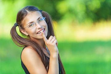 smiling young woman put finger to his lips