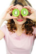 Young woman holding kiwi fruit for her eyes