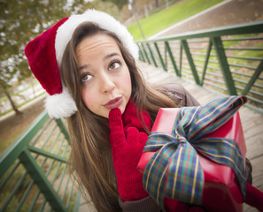 Pretty Woman Wearing a Santa Hat with Wrapped Gift