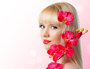 Beautiful blonde young girl with red orchid flowers