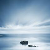 Fototapety Dark rocks in a blue ocean under cloudy sky in a bad weather.