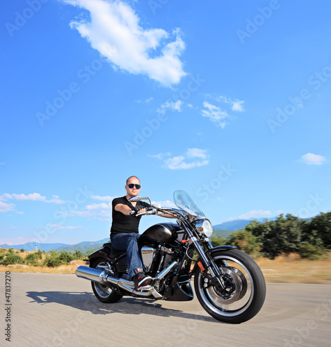 A biker riding a customized motorcycle on an open road