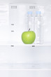 A green apple and bottles of water in a fridge