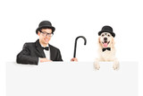 A performer in suit, retro hat and cane posing with dog behind a