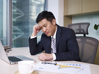 frustrated asian businessman thinking in office