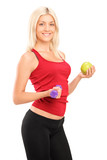 Attractive female athlete holding dumbbell and apple