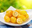 Yellow kumquat on nature background.
