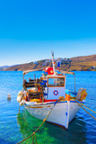 Colorful side front view of wooden fishing boat at Santorini Isl