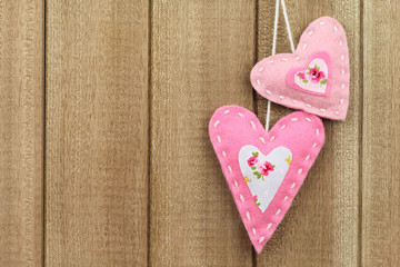 Two hearts hanging on wooden background