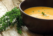Cream soup with carrot and pumpkin decorated with thyme