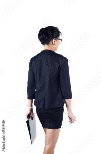 Back view of business woman holding folder and pen.