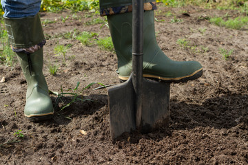 digging in green boots, close-up