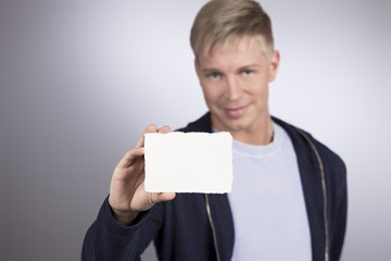 Smiling man presenting empty white card.
