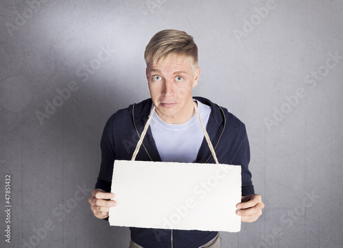 Unhappy man holding empty signboard with space for text.