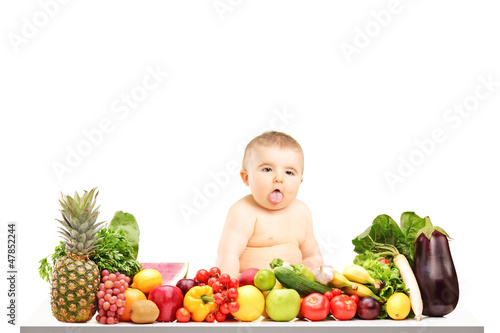 Baby boy sitting on a table full of different fruits and vegetab