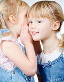 Little girls sharing a secret