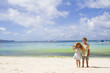 two children - boy and girl - on tropical beach and sea backgrou
