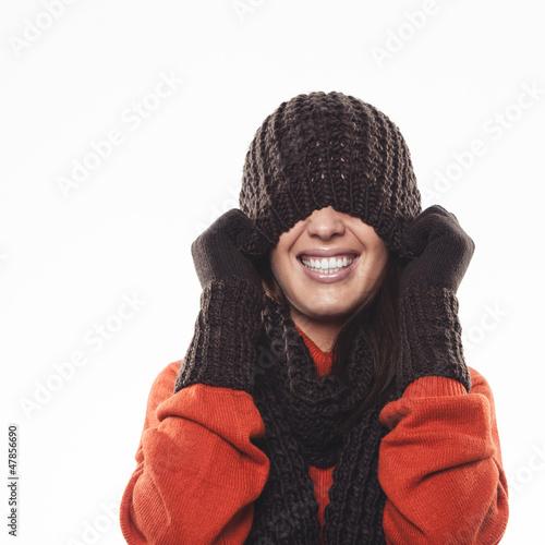 Frau versteckt sich unter Strickmütze