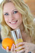 Smiling blond woman drinking orange juice