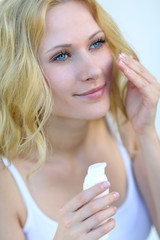 Portrait of beautiful woman applying moisturizer