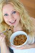 Smiling blond girl eating cereals for breakfast