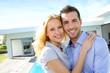 Cheerful couple standing in front of modern house
