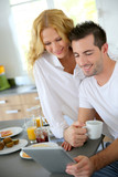 Young couple using digital tablet at breakfast time