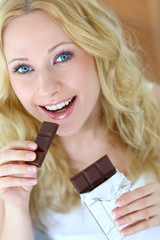 Blond woman eating chocolate bar