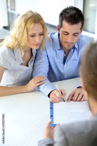 Cheerful couple signing property contract with real-estate agent