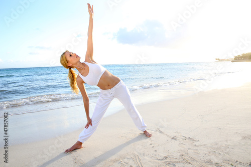 Beautiful woman doing yoga exercises by the beach
