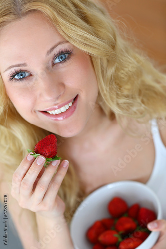Attractive blong girl eating strawberries