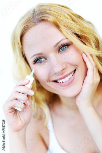 Smiling woman applying concealer in front of mirror