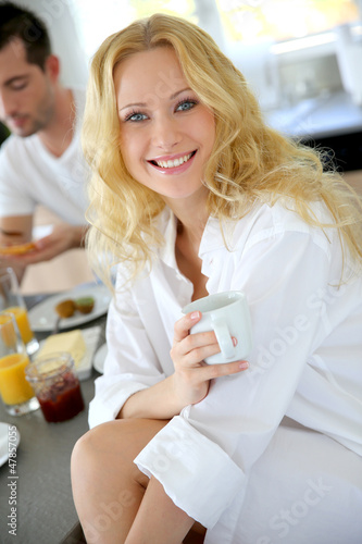 Beautiful blond girl drinking coffee for breakfast
