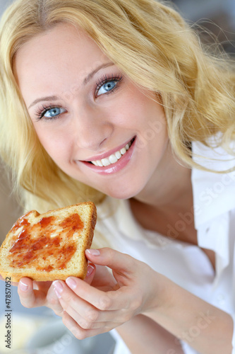 Beautiful girl eating toasted bread for breakfast