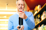 Man holding a bottle of red wine