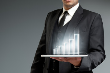 Financial report & statistics. Bar graph on tablet pc.