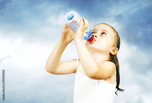 A little sweet girl drinks water from a bottle
