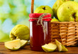 jar of jam and quinces with leaves in basket,
