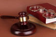 Gavel, handcuffs and.book on law on brown background