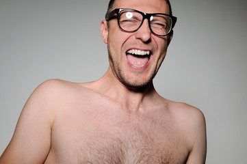 Young man in glasses laughing happily