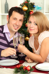 Young happy couple holding glasses with champagne at table near