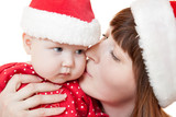 Mother kissing her child in Christmas hat
