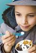 Cute teenage boy eating ice cream with chocolate topping