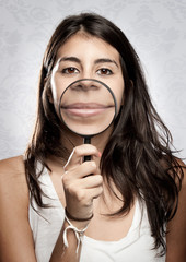 woman showing mouth through magnifying glass